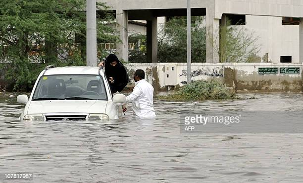 A Saudi man and a woman leave their car after it got stuck in a flooded street following heavy rain in the Red Sea port city of Jeddah on December 30...