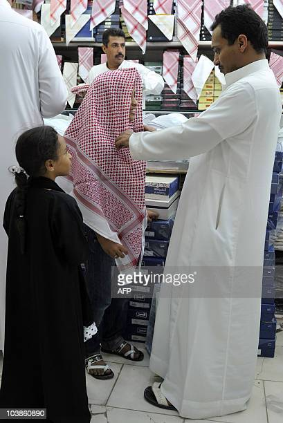 A Saudi man buys a new keffiyeh the traditional chequerred headdress for his son at a specialised shop in the Saudi Red Sea port of Jeddah late on...