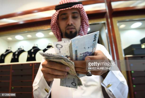 A Saudi man counts banknotes at his jewelry shop at Tiba market in Riyadh on October 3 2016 Since 2014 global oil prices have collapsed by more than...