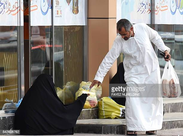 A Saudi man hands money to a woman begging outside a supermarket on a main street in the Saudi capital Riyadh on June 20 2016 Charity is one of the...