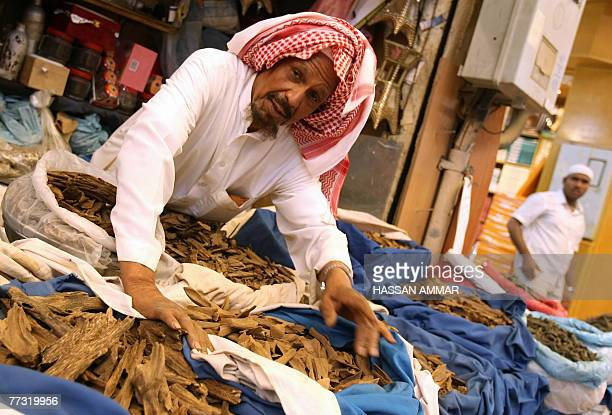 A Saudi man leans over sacks of aromatic Oud or Agarwood at a shop in Riyadh 10 October 2007 Oud also known by the names Agrawood and Aloeswood in...