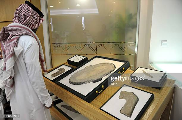 Saudi man looks at archaeological artefacts displayed during a news conference in the Red Sea city of Jeddah on August 24, 2011. Saudi Arabia has...