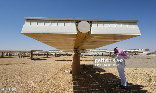 Saudi man talks on his mobile under the shade of solar panel at a solar plant in Uyayna north of Riyadh on March 29 2018 On March 27 Saudi announced...