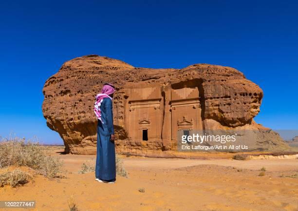 Saudi man walking in front of tombs in al-Hijr archaeological site in Madain Saleh, Al Madinah Province, Alula, Saudi Arabia on December 28, 2019 in...
