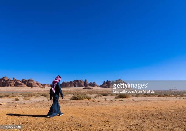 Saudi man walking in Madain Saleh, Al Madinah Province, Alula, Saudi Arabia on December 28, 2019 in Alula, Saudi Arabia.