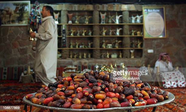 A Saudi man walks past a plate of dates in a tent in the Hael desert around 700 kms north of downtown Riyadh 02 June 2007 Known for its old forts and...