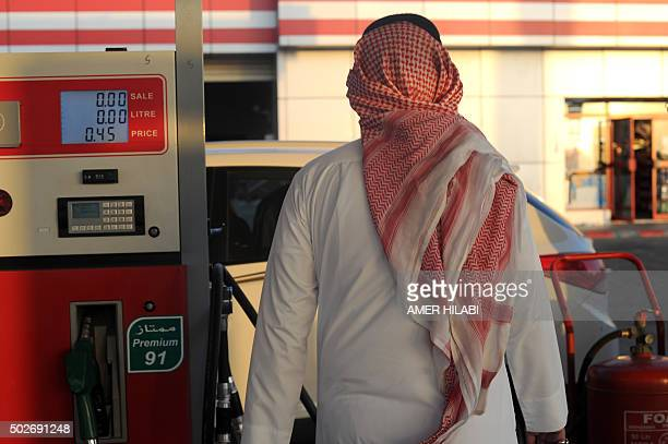 A Saudi man walks past a pump at a petrol station on December 28 2015 in the Red Sea city of Jeddah Saudi Arabia said it plans to review the prices...