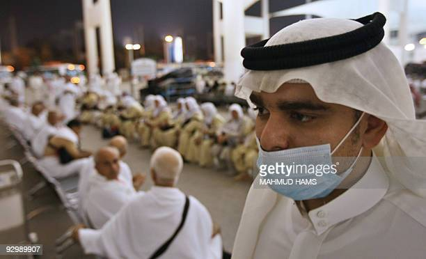 A Saudi man wearing a mask for protection against swine flu walks past Turkish and Iranian Muslim pilgrims at Jeddah airport upon their arrival on...