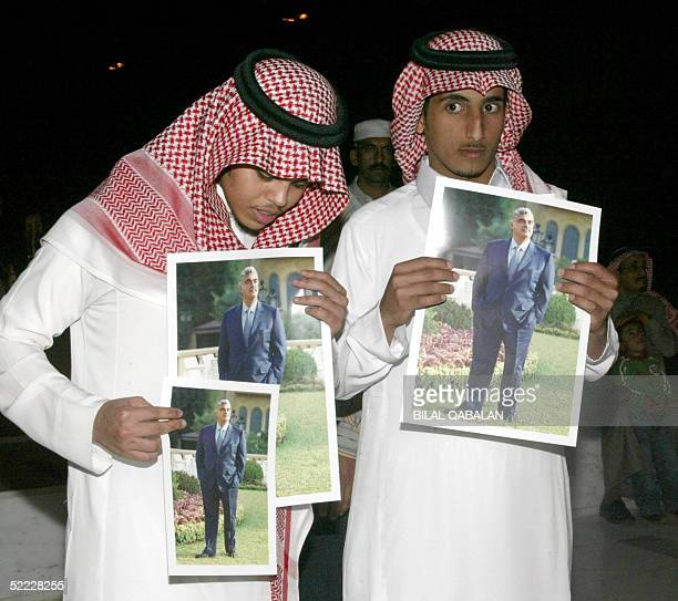 Saudi men carry pictures of slain former prime minister Rafiq Hariri as they as people gather to offer their condolences to his family in Riyadh 22...