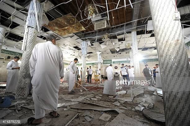 Saudi men gather around debris following a blast inside a mosque in the mainly Shiite Saudi Gulf coastal town of Qatif 400 kms east of Riyadh on May...