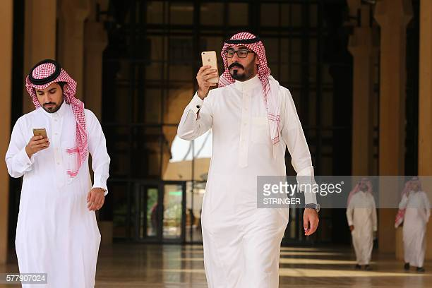 Saudi men play with the Pokemon Go application on their mobiles in the capital Riyadh on July 17 2016 / AFP / STRINGER