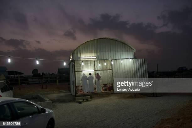 Saudi men pray at dusk at a camel market outside of Riyadh Saudi Arabia March 1 2013 Despite an extremely wealthy sector of society in Saudi Arabia...