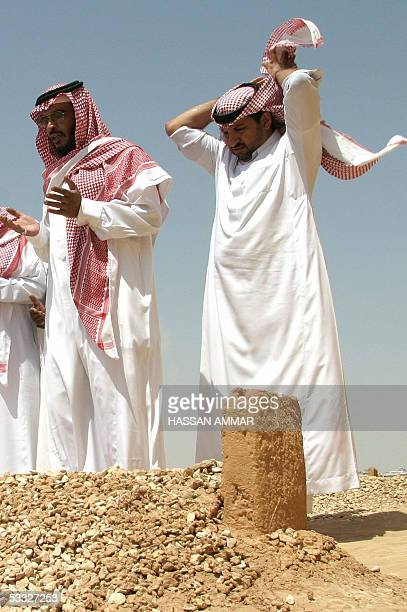 Saudi men pray over the grave of King Fahd of Saudi Arabia after Friday prayers in Riyadh 05 August 2005 In keeping with the strict Muslim traditions...