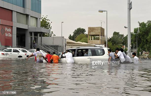 Saudi men push a car stuck in a flooded street following heavy rain in the Red Sea port city of Jeddah on December 30 2010 AFP PHOTO/AMER HILABI