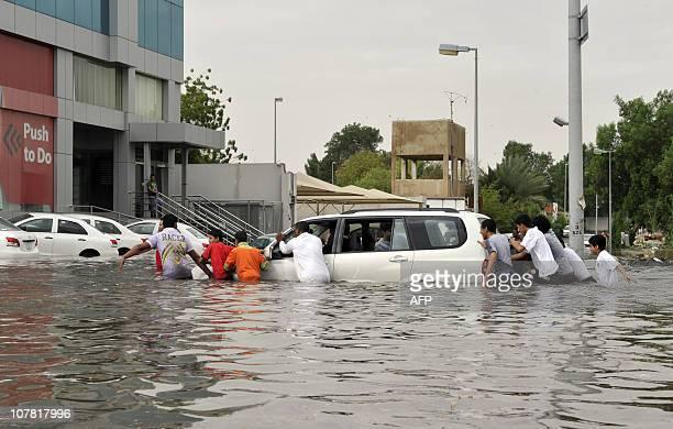 Saudi men push a car stuck in a flooded street following heavy rain in the Red Sea port city of Jeddah on December 30 2010 AFP PHOTO/AMER HILABI