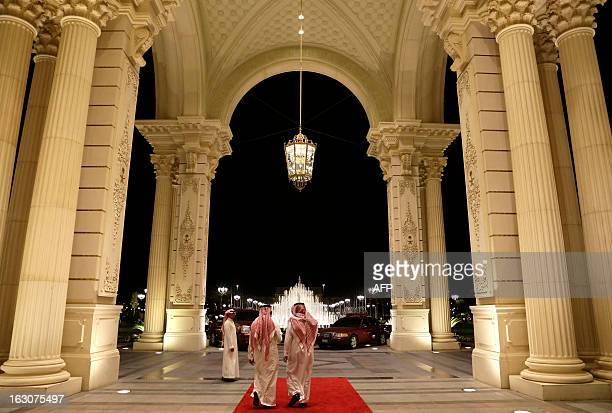 Saudi men walk out of the entrance to the RitzCarlton Hotel where US Secretary of State John Kerry is staying in Riyadh on March 4 2013 From Saudi...