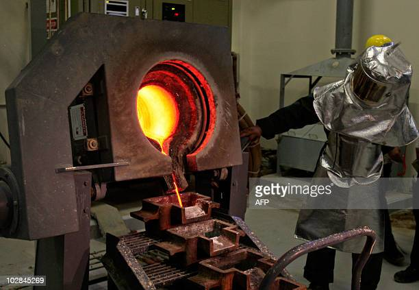 A Saudi mine worker pours a stream of molten gold from the furnace into moulds to produce gold ingots during a press tour at the AlAmar Gold Mine...