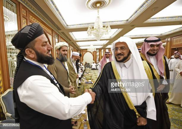 Saudi minister of Islamic affairs Abdullatif Al-Sheikh shakes hands with an Afghan cleric during the international Ulema conference on peace and...