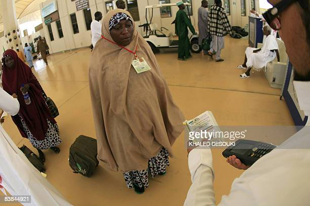 A Saudi official checks the documents of a Nigerian Muslim pilgrim as she leaves the King Abdul Aziz airport in the Red Sea port city of Jeddah on...