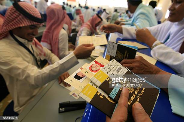 A Saudi official gives bus tickets to Indonesian Muslim pilgrims upon their arrival to King Abdul Aziz airport in the Red Sea port city of Jeddah on...