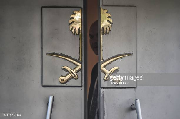 Saudi official look through the door of the Saudi Arabian consulate in Istanbul on October 8, 2018 in Istanbul during a demonstration for missing...