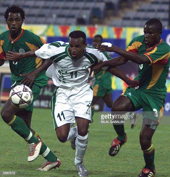 Saudi Olympic team player Saleh Bashir fights for the ball against Senegalese Olympic team players Abed Sylla and Osman Teita during their national...