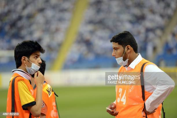 Saudi photographers wear mouth and nose masks during a football match at the King Fahad stadium on April 22 2014 in Riyadh The health ministry...