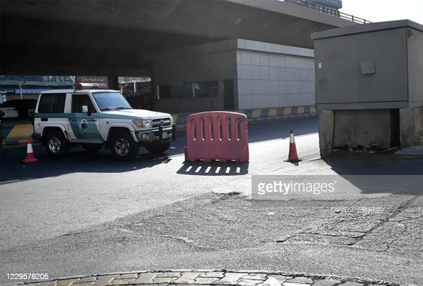 Saudi police close a street leading to a non-Muslim cemetery in the Saudi city of Jeddah where a bomb struck a World War I commemoration attended by...