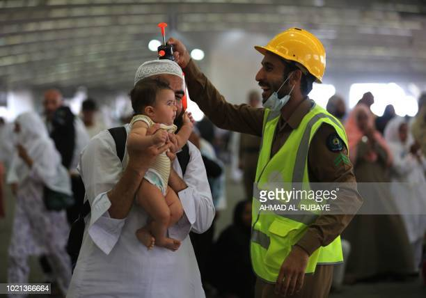 A Saudi police officer smiles at a pilgrim holding a child as they take part in the symbolic stoning of the devil at the Jamarat Bridge in Mina near...