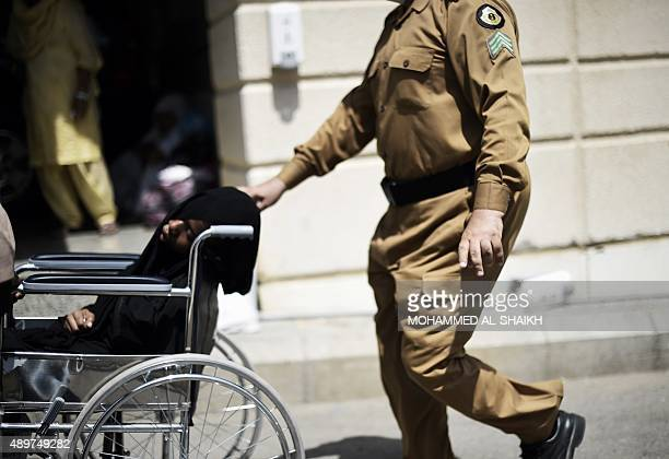 A Saudi policeman pushes a wheelchair with an injured pilgrim outside an emergency hospital following a deadly stampede in Mina near the holy city of...