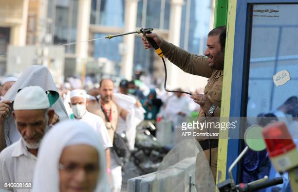 A Saudi policeman spays Muslim pilgrims with water to cool them off near the Grand Mosque in the holy Saudi city of Mecca on August 29 on the eve of...