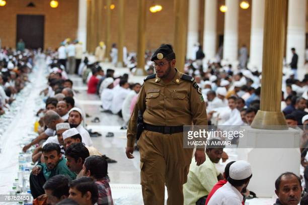 A Saudi policeman walks between foreign workers wait to break their fast on the first Friday of Ramadan at the Imam Turki bin Abdullah mosque in...