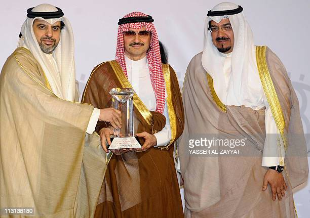 Saudi Prince Alwaleed bin Talal receives an award from Madi Khamis secretary general of the Arab Media Forum and Kuwaiti Oil and Information Minister...