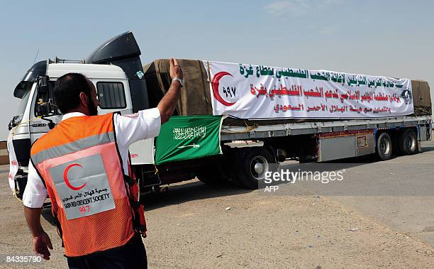 Saudi Red Crescent worker clears the way for a shipment of humanitarian aid supplies from the Organisation of Islamic Conference to the Gaza Strip in...