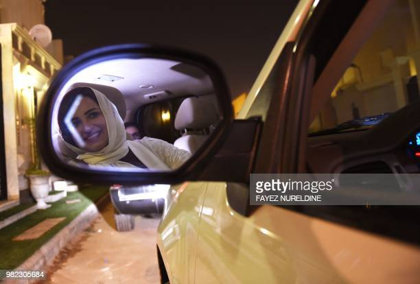 Saudi Samar Almogren is seen in her car's rearview mirror as she drives through Riyadh city's streets for the first time just after midnight June 24...