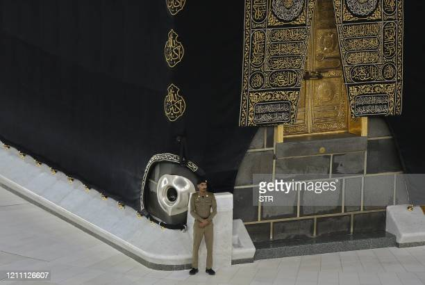 A Saudi security guard stands guard as worshippers perform Isha prayer next to the Kaaba in Mecca's Grand Mosque Islam's holiest site on April 27...