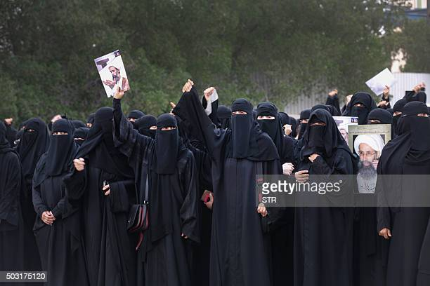 Saudi Shiite women hold placards bearing a portrait of prominent Shiite Muslim cleric Nimr alNimr during a protest in the eastern coastal city of...