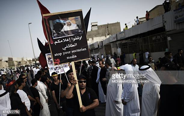 Saudi Shiites hold placards during a mass funeral in the village of Kudeih in the mainly Shiite Saudi eastern Gulf governorate of Qatif 400 kms east...