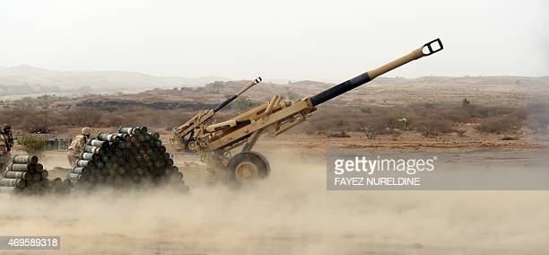 Saudi soldiers from an artillery unit prepare a cannon to fire shells towards Yemen from a position close to the Saudi-Yemeni border, in Saudi...