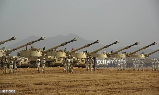 Saudi soldiers stand at attention in front of tanks during a visit by Deputy Defence Minister Prince Khaled bin Sultan at AlKhoba in the southern...