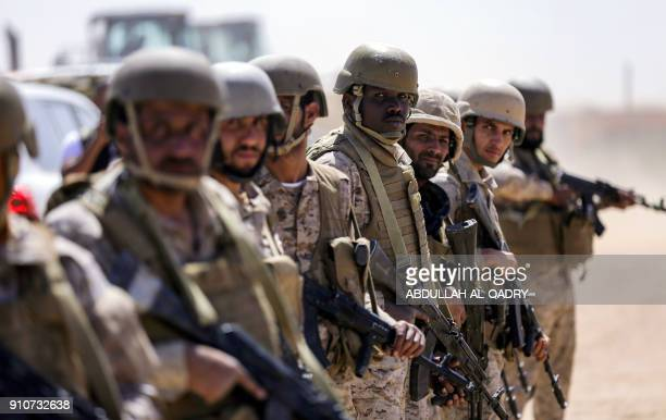 Saudi soldiers stand by in an airfield as a Saudi Air Force cargo plane lands at an airfield in Yemen's northeastern province of Marib on January 26...