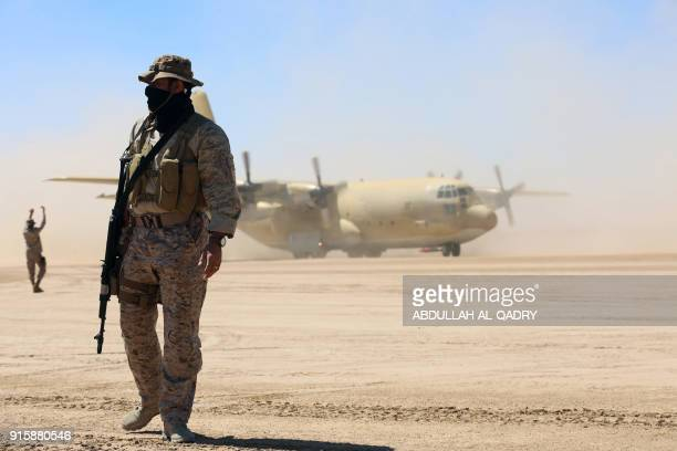 TOPSHOT Saudi soldiers stand guard as a Saudi air force cargo plane carrying aid lands at an airfield in Yemen's central province of Marib on...