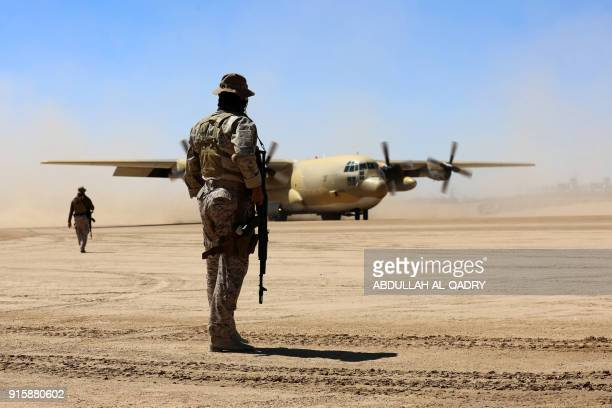Saudi soldiers stand guard as a Saudi air force cargo plane carrying aid lands at an airfield in Yemen's central province of Marib on February 8 2018