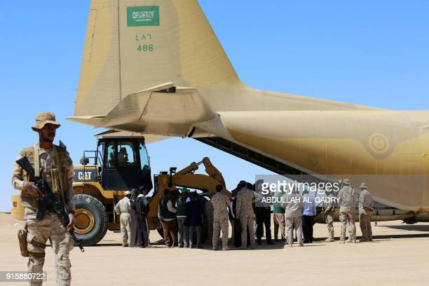 Saudi soldiers stand guard as workers unload aid from a Saudi air force cargo plane at an airfield in Yemen's central province of Marib on February 8...