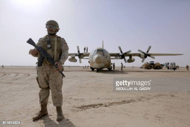 Saudi soldiers stand guard as workers unload aid packages from a Saudi air force cargo plane at an airfield Yemen's central province of Marib on...