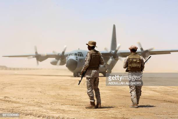 Saudi soldiers stand guard before aid supplies are unloaded from a Saudi air force cargo plane at an airfield in Yemen's central province of Marib on...