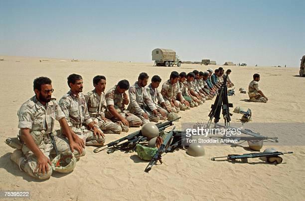 A Saudi tank crew prays toward Mecca on the frontline between Saudi Arabia and Kuwait during the Gulf War 1990