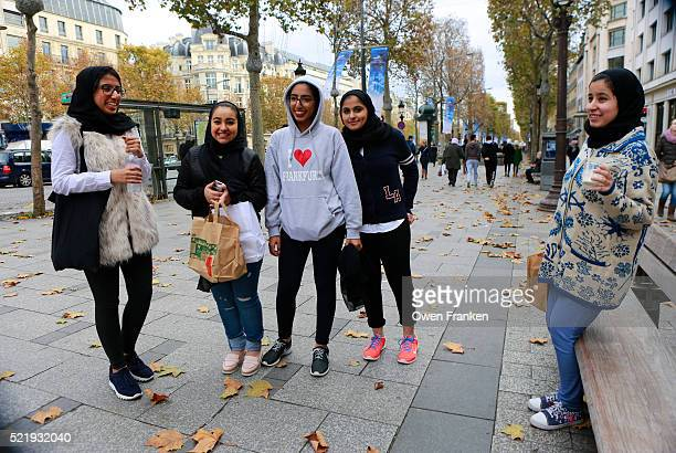 Saudi teenage girls on the Champs Elysees, Paris - dressed in modern teenager fashion except for wea