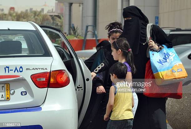 Saudi woman and her children get into a taxi in Riyadh on June 14 three days before a June 17 nationwide campaign by Saudi women who are planning to...