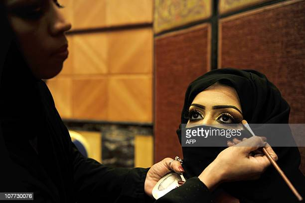A Saudi woman applies makeup on a model during a beauty and style competition on the sidelines of the 2010 Cosmetic Expo a fourday exhibition held...